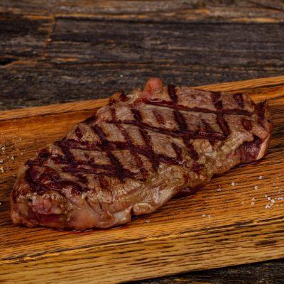 steak on wooden board with salt and pepper